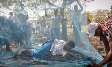 Health workers demonstrate bednets, Courtesy of Sven Torffin, WHO World Malaria Day 2017